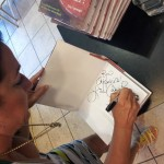 Lisa autographs a book